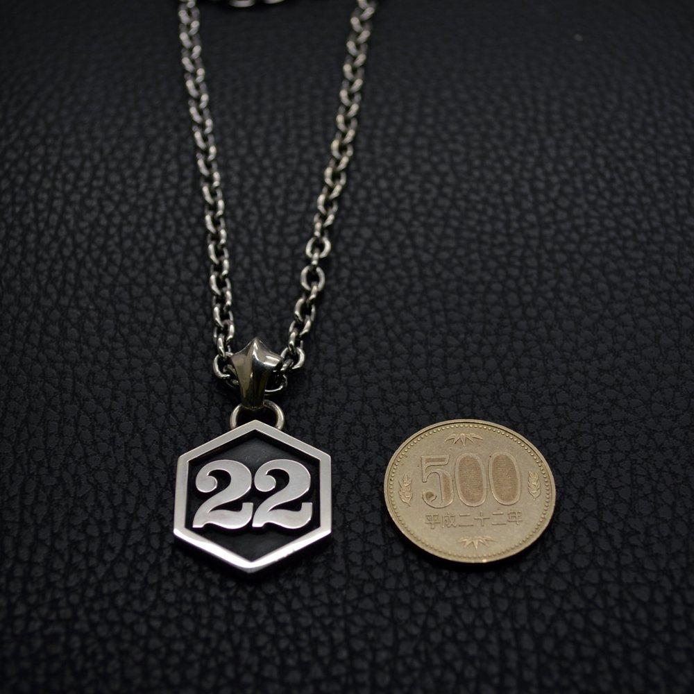 背番号ネックレスの大きさを500円玉と比較している写真