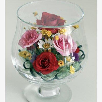 色とりどりのかわいいバラとノースポールをアレンジした春らしいグラスSのボトルフラワー
